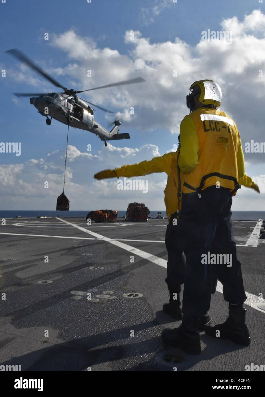 SOUTH CHINA SEA (March 20, 2019) - Boatswain's Mate 2nd Class Tyjhay McCain, from South Bend, Ind., and Boatswain's Mate Seaman Shawn Bernard Jr., from Atlanta, launch an MH-60S Sea Hawk helicopter from the Golden Falcons of Helicopter Sea Combat Squadron 12 during a vertical replenishment aboard U.S. 7th Fleet Flagship USS Blue Ridge (LCC 19). Blue Ridge is the oldest operational ship in the Navy and, as 7th Fleet command ship, actively works to foster relationships with allies and partners in the Indo-Pacific Region. - Stock Image