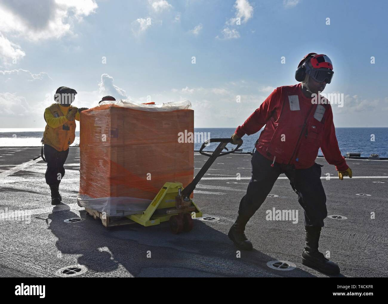 SOUTH CHINA SEA (March 20, 2019) - Logistics Specialist Seaman Zikeya Hammond-Douglas, from Philadelphia, and Boatswain's Mate Seaman Shawn Bernard Jr., from Atlanta, clear the ship's flight deck of delivered supplies during a vertical replenishment aboard U.S. 7th Fleet Flagship USS Blue Ridge (LCC 19). Blue Ridge is the oldest operational ship in the Navy and, as 7th Fleet command ship, actively works to foster relationships with allies and partners in the Indo-Pacific Region. - Stock Image