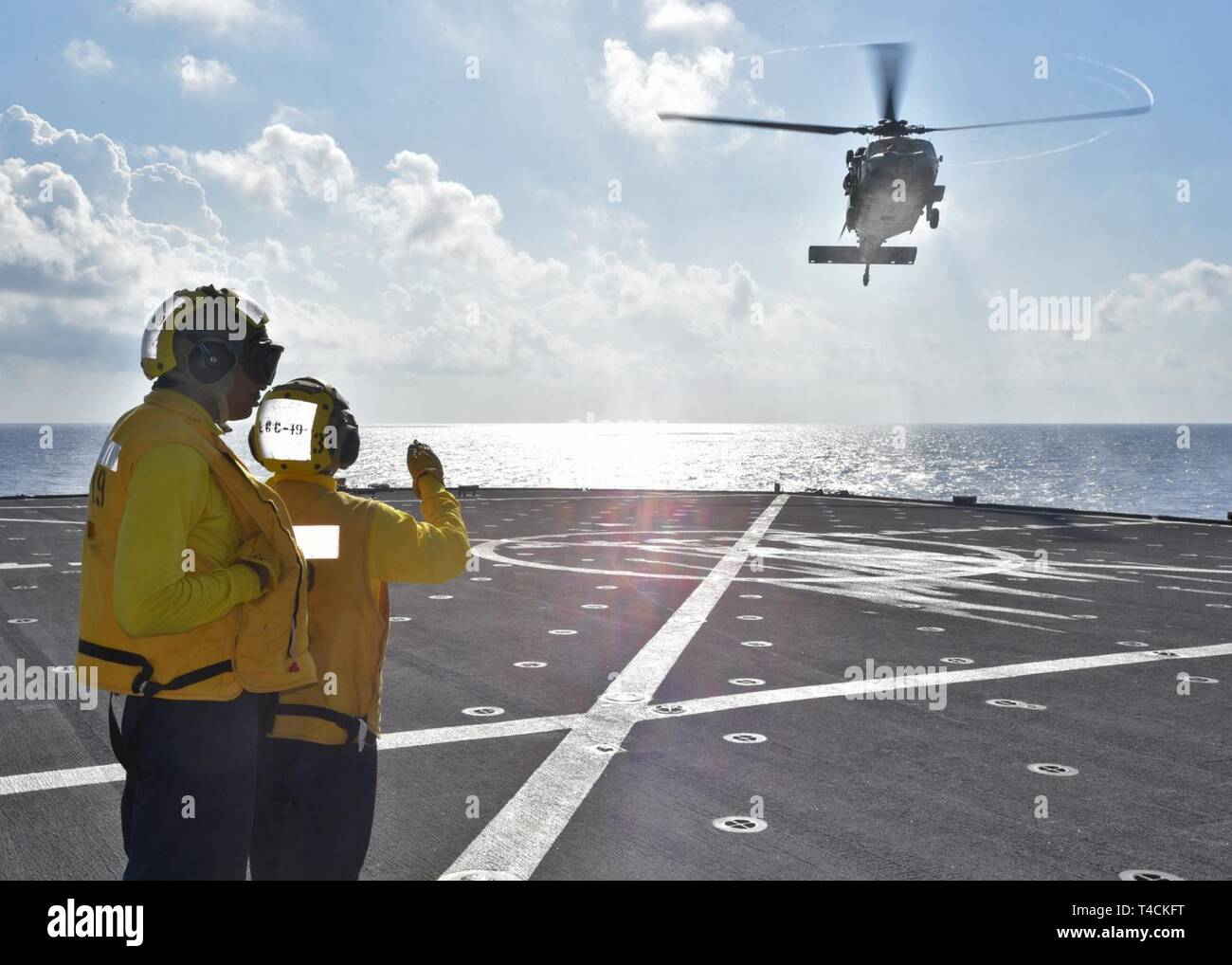 SOUTH CHINA SEA (March 20, 2019) - Boatswain's Mate 2nd Class Tyjhay McCain, from South Bend, Ind., and Boatswain's Mate Seaman Shawn Bernard Jr., from Atlanta, launch a MH-60S Sea Hawk helicopter from the Golden Falcons of Helicopter Sea Combat Squadron 12 during a vertical replenishment aboard U.S. 7th Fleet Flagship USS Blue Ridge (LCC 19). Blue Ridge is the oldest operational ship in the Navy and, as 7th Fleet command ship, actively works to foster relationships with allies and partners in the Indo-Pacific Region. - Stock Image
