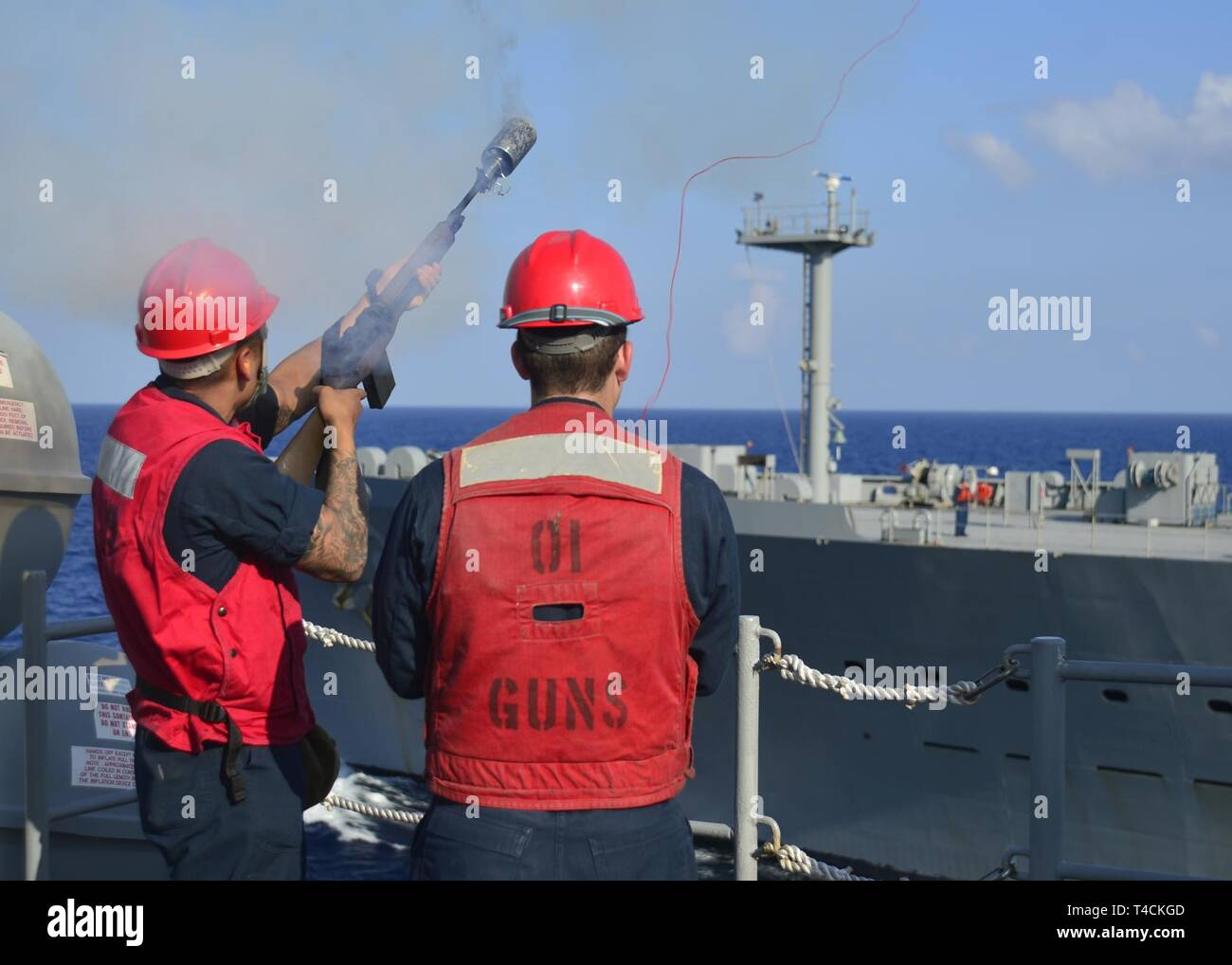 SOUTH CHINA SEA (March 20, 2019) - Gunner's Mate 3rd Class Erik Renteria, from Richardson, Texas., fires line to Fleet Replenishment Oiler USNS Guadalupe (T-AO 200) during a replenishment-at-sea with U.S. 7th Fleet Flagship USS Blue Ridge (LCC 19). Blue Ridge is the oldest operational ship in the Navy and, as 7th Fleet command ship, actively works to foster relationships with allies and partners in the Indo-Pacific Region. - Stock Image