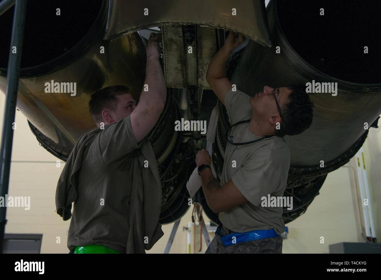 From left, Staff Sgt. Shane Vandevelde and Senior Airman Pfeenix Tramill, 5th Maintenance Squadron crew chiefs, adjust fasteners on a B-52H Stratofortress engine at Minot Air Force Base, North Dakota, March 19, 2019. During a Phase Inspection, a B-52 is stripped down to its basic body frame. - Stock Image