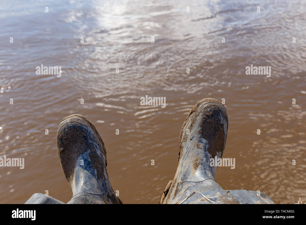 Feet of a traveler or wild nature explorer in black dirty boots sitting on the bank of the river - Stock Image