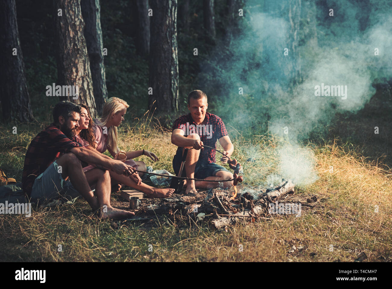Two couples camping in woods. Cooking sausages on campfire. Warm summer evening in forest Stock Photo
