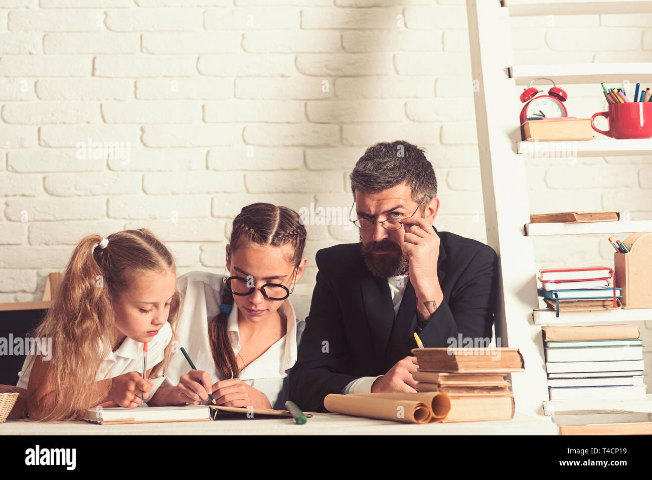 School time of girl sisters with father. Father helps children to study at home. Back to school and home schooling. Teacher man and small girls Stock Photo