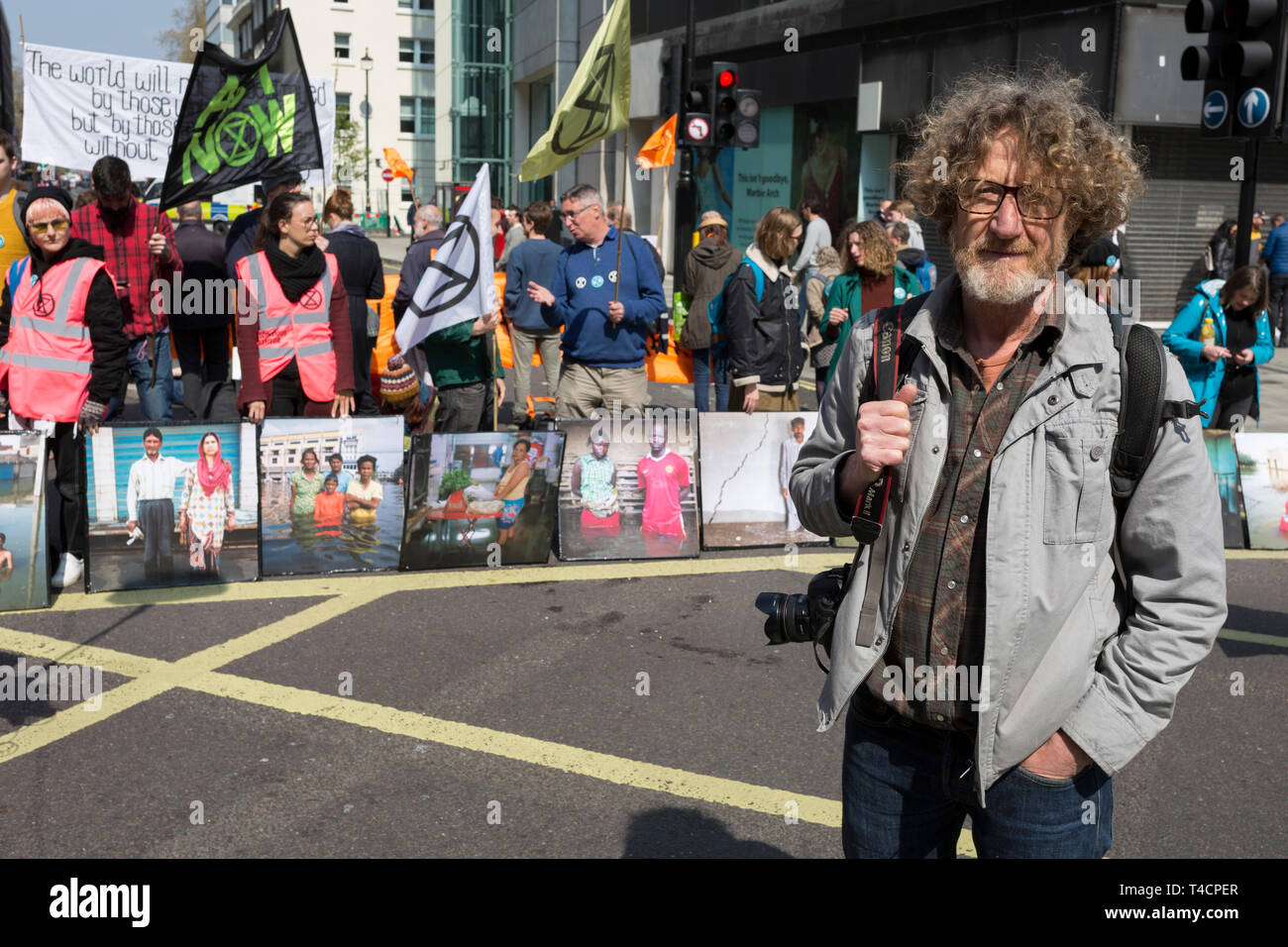 Photographer Gideon Mendel and some of his flood victim portraits 'Drowning World' during the climate Change protest with Extinction Rebellion blocking Oxford Street and simultaneously stop traffic across central London including Marble Arch, Piccadilly Circus, Waterloo Bridge and roads around Parliament Square, on 15th April 2019, in London, England. Stock Photo
