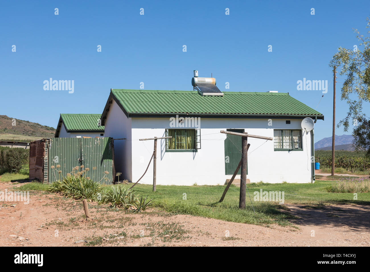 Farm worker's cottage with roof mounted solar hot water geyser for renewable energy and heating, South Africa - Stock Image