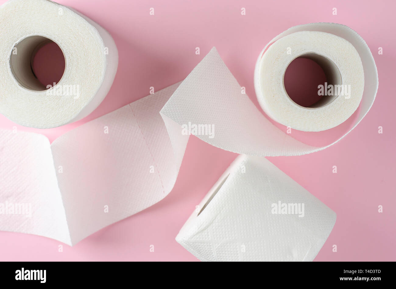 White toilet paper rolls on pastel pink background. Space for text. Hygienic and everyday use object. - Stock Image