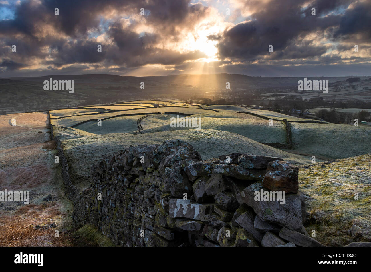 The View From the Ancient Tumulus of Kirkcarrion as Crepuscular Rays Sweep across the Frost Coated Fields Below, Lunedale, Teesdale, County Durham, UK - Stock Image