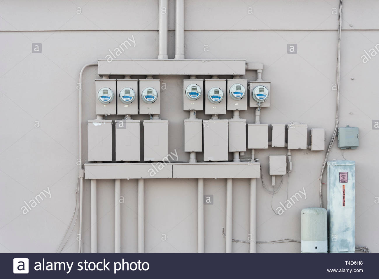 Seven electricity meter boxes on beige wall deadpan photography - Stock Image