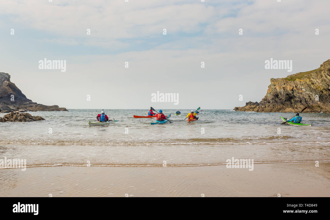 Landscape shot of group of adults kayaking off the Welsh coastline, Anglesey - Stock Image