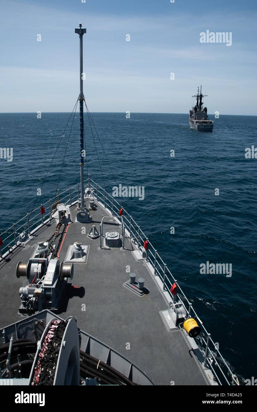 SOUTH CHINA SEA (March 21, 2019) The Avenger class mine countermeasures ship USS Chief (MCM 14) steams behind Philippine Navy vessel BRP Ramon Alcaraz (FF 16) during a maritime cooperative activity. Chief, part of Mine Countermeasures Squadron 7, is operating in the Indo-Pacific region to enhance interoperability with partners and serve as a ready-response platform for contingency operations. - Stock Image