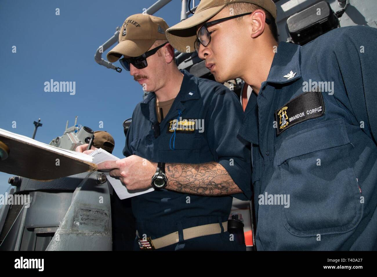 SOUTH CHINA SEA (March 21, 2019) Lt. j. g. Russell Pattison (left), from Perryton, Texas, and Quartermaster 3rd Class Brandon Corpuz, from San Diego, California, translate flashing-light Morse code received from Philippine Navy vessel BRP Ramon Alcaraz (FF 16) aboard the Avenger class mine countermeasures ship USS Chief (MCM 14) during a maritime cooperative activity. Chief, part of Mine Countermeasures Squadron 7, is operating in the Indo-Pacific region to enhance interoperability with partners and serve as a ready-response platform for contingency operations. - Stock Image