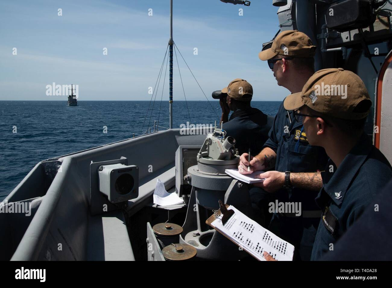 SOUTH CHINA SEA (March 21, 2019) Sailors translate flashing-light Morse code received from Philippine Navy vessel BRP Ramon Alcaraz (FF 16) aboard the Avenger class mine countermeasures ship USS Chief (MCM 14) during a maritime cooperative activity. Chief, part of Mine Countermeasures Squadron 7, is operating in the Indo-Pacific region to enhance interoperability with partners and serve as a ready-response platform for contingency operations. - Stock Image