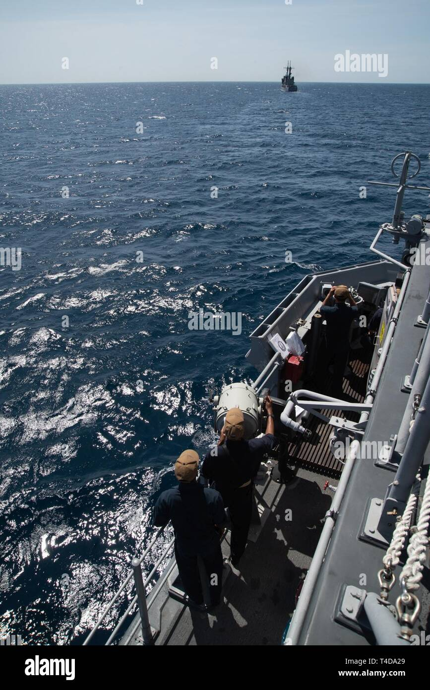 SOUTH CHINA SEA (March 21, 2019) Sailors use flashing-light Morse code aboard the Avenger class mine countermeasures ship USS Chief (MCM 14) to communicate with Philippine Navy vessel BRP Ramon Alcaraz (FF 16) during a maritime cooperative activity. Chief, part of Mine Countermeasures Squadron 7, is operating in the Indo-Pacific region to enhance interoperability with partners and serve as a ready-response platform for contingency operations. - Stock Image