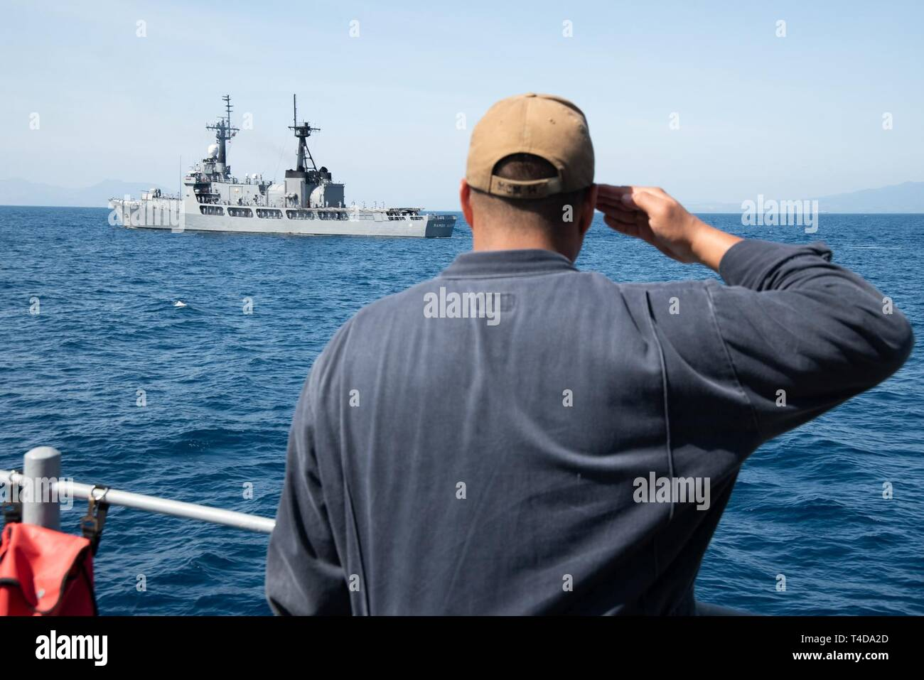 SOUTH CHINA SEA (March 21, 2019) Machinist Mate 1st Class Blaze Featheran, from Kaneohe, Hawaii, renders honors to Philippine Navy vessel BRP Ramon Alcaraz (FF 16) after completing a maritime cooperative activity aboard the Avenger class mine countermeasures ship USS Chief (MCM 14). Chief, part of Mine Countermeasures Squadron 7, is operating in the Indo-Pacific region to enhance interoperability with partners and serve as a ready-response platform for contingency operations. - Stock Image