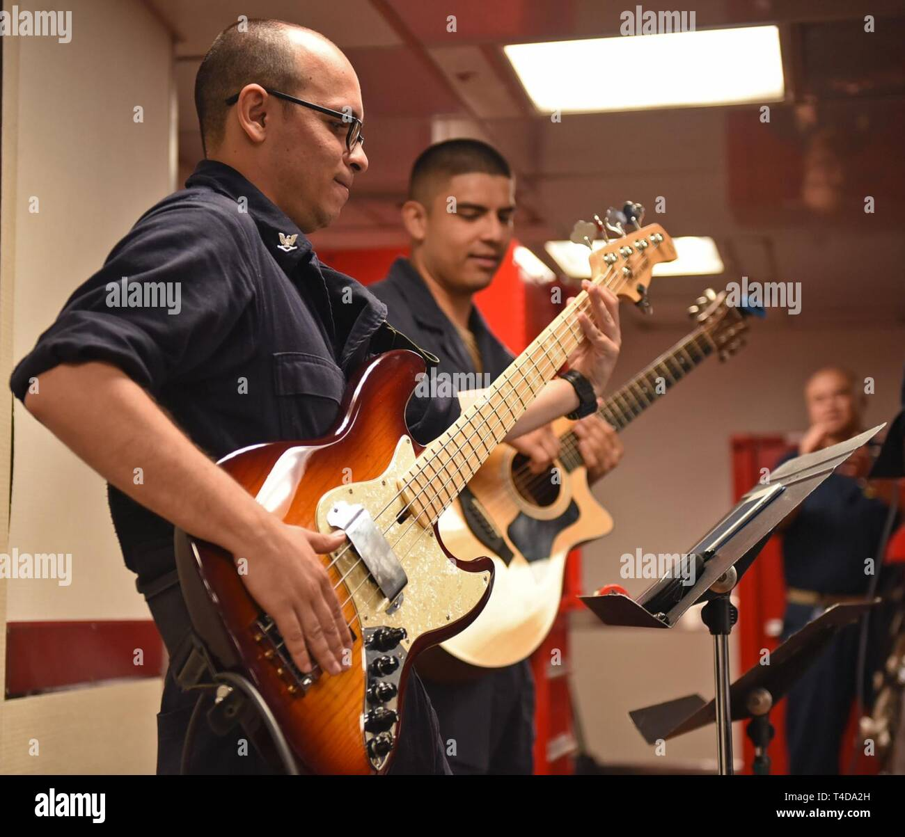 SOUTH CHINA SEA (March 22, 2019) - Musician 3rd Class Jose Figueroa, from Ponce, P.R., and Musician Seaman Jorge Cabrera, from Los Angeles, performs with the 7th Fleet Band, Far East Edition during a Women's History Month celebration on the mess decks of U.S. 7th Fleet Flagship USS Blue Ridge (LCC 19). Blue Ridge is the oldest operational ship in the Navy and, as 7th Fleet command ship, actively works to foster relationships with allies and partners in the Indo-Pacific Region. - Stock Image