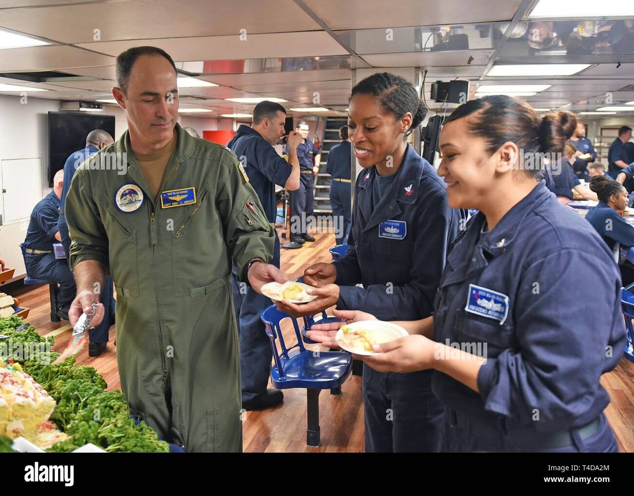 SOUTH CHINA SEA (March 22, 2019) - Capt. Eric J. Anduze, commanding officer of U.S. 7th Fleet Flagship USS Blue Ridge (LCC 19), serves cake to members of the crew during a Women's History Month celebration on the ship's mess decks. Blue Ridge is the oldest operational ship in the Navy and, as 7th Fleet command ship, actively works to foster relationships with allies and partners in the Indo-Pacific Region. - Stock Image