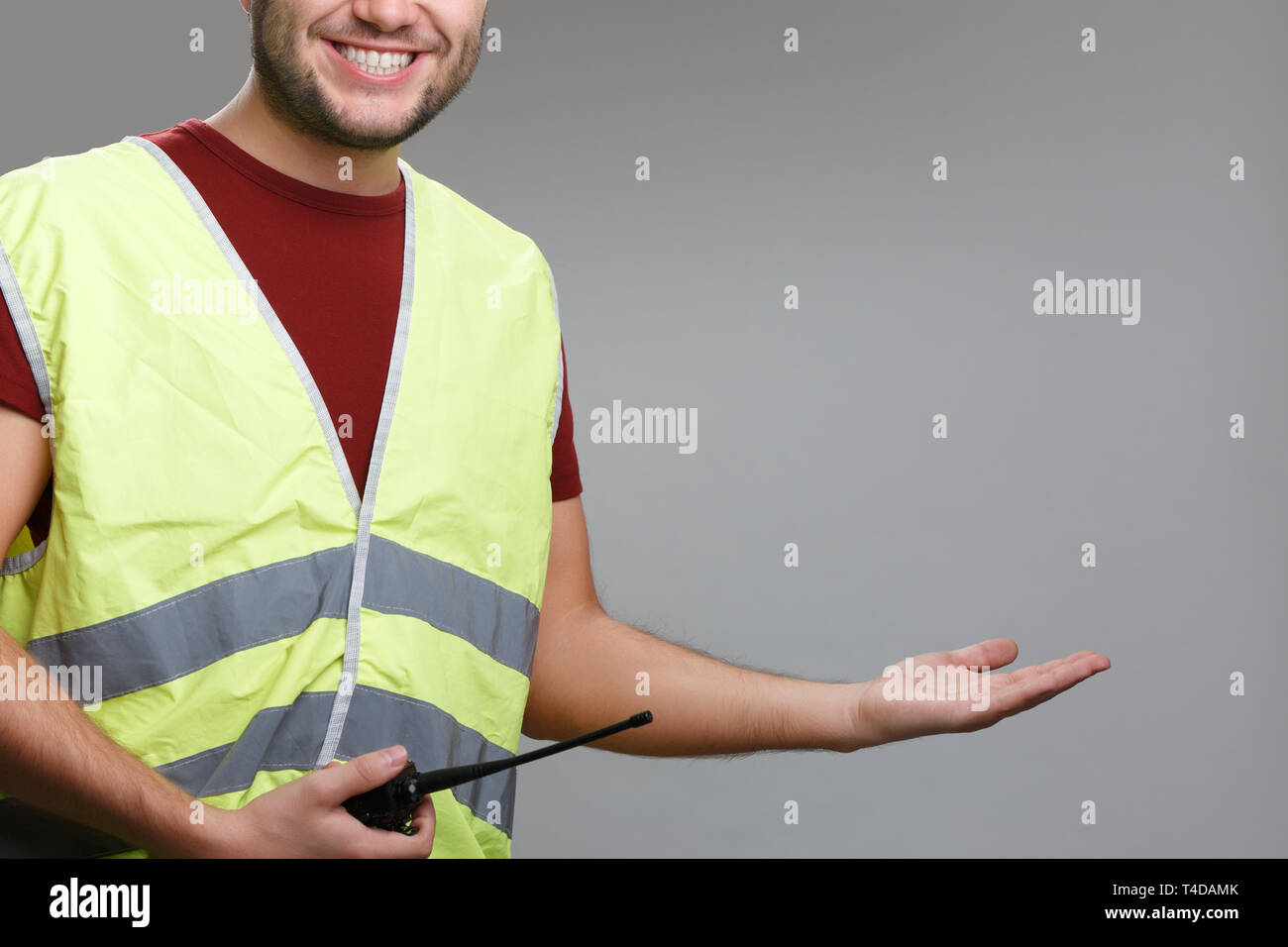Photo of smiling builder in yellow vest with raised palm up - Stock Image