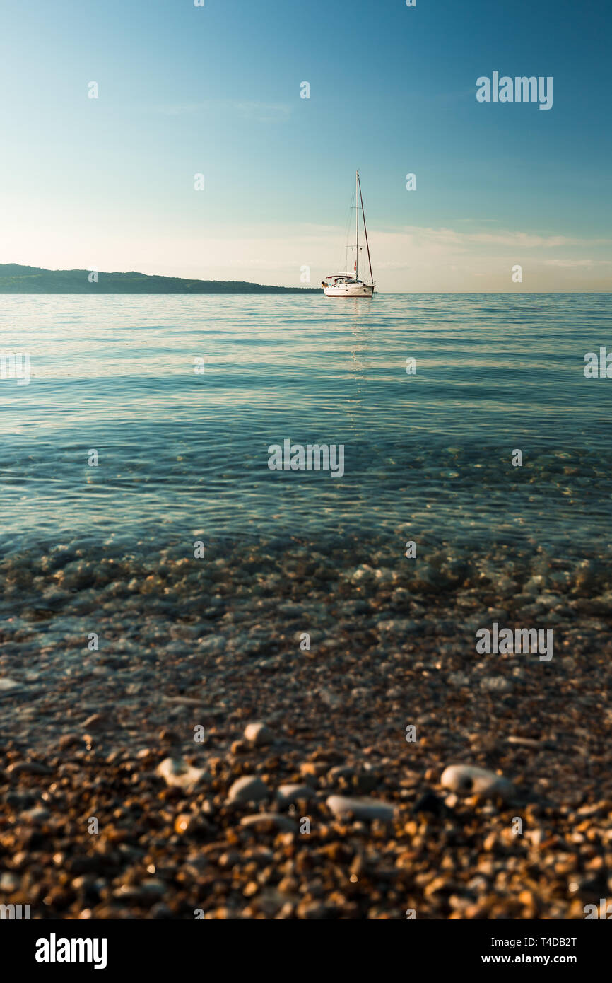 Sailing boat on a clear blue morning in the Ionian sea at a rocky beach on Corfu with clear blue water (Corfu, Greece, Europe) - Stock Image
