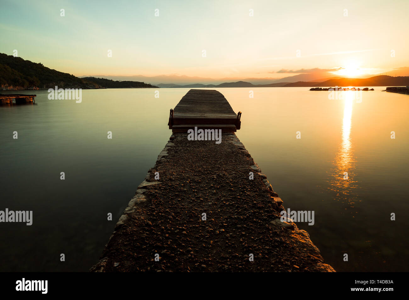 Sunrise over a little wooden pier in calm water with yellow tones, rising sun and majestic mountains (Kalami, Corfu, Greece, Europe) - Stock Image
