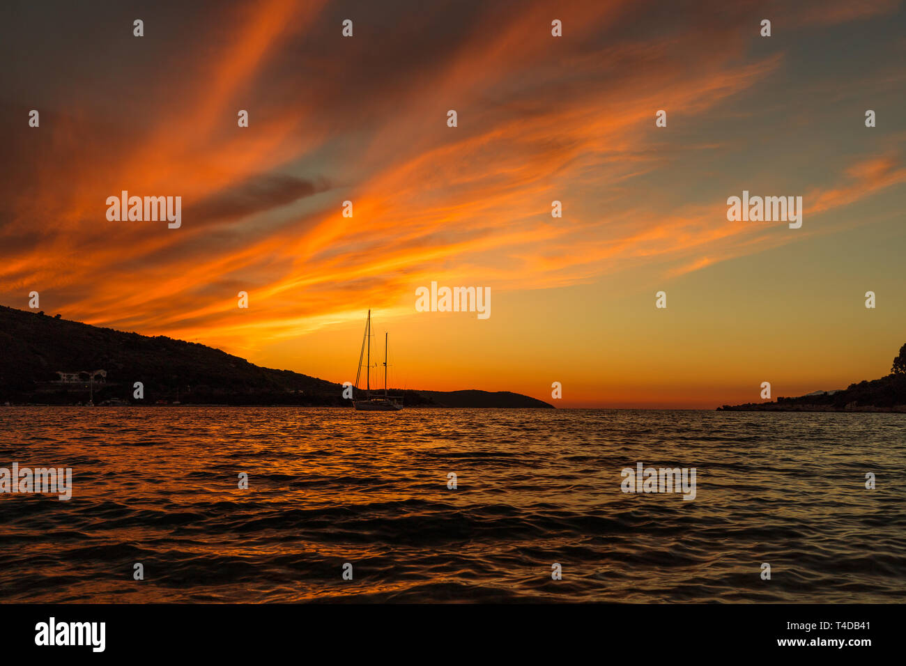 Dramatic red and orange sunset over the sea with mountain range background and yacht on the water (Kassiopi, Corfu, Greece, Europe) Stock Photo