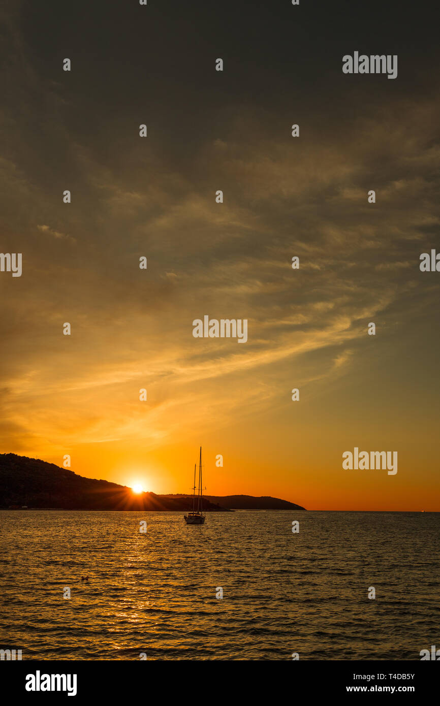 Dramatic red and orange sunset over the sea with mountain range background and yacht on the water (Kassiopi, Corfu, Greece, Europe) - Stock Image
