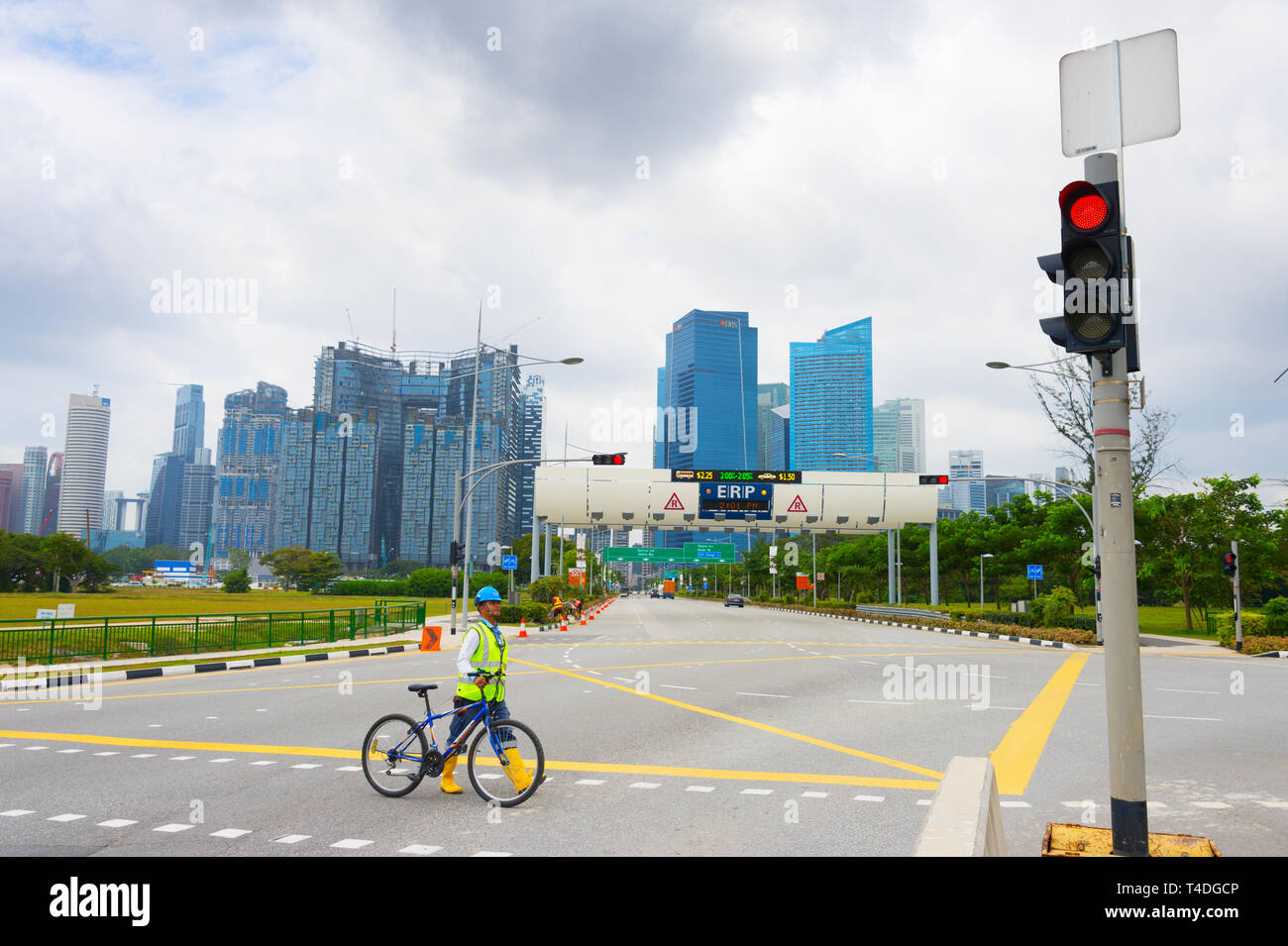 SINGAPORE - FEBRUARY 16, 2017: Construction site worker in helmet and vest crossing road with bicycle, Singapore downtown skyline in background - Stock Image