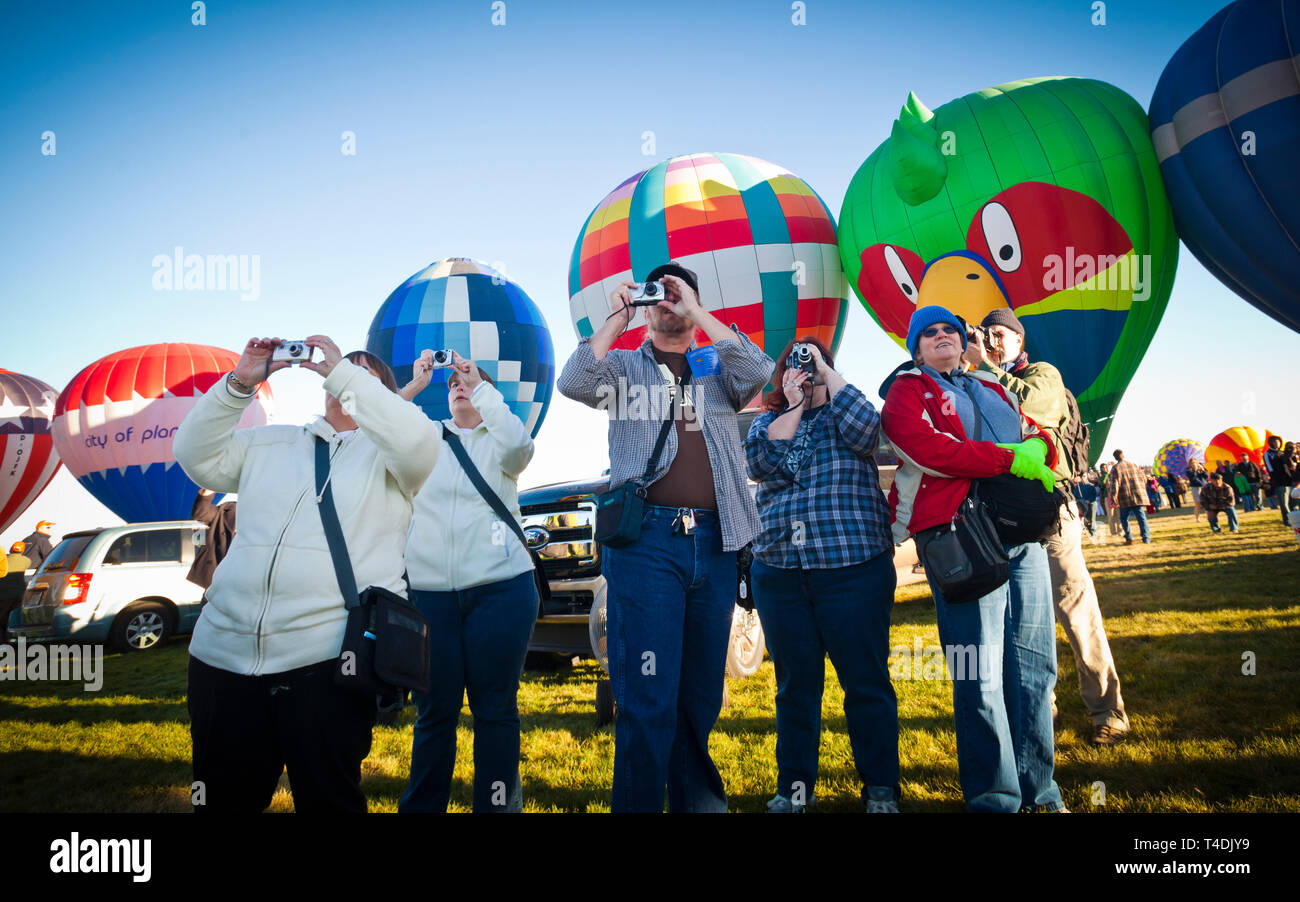 Onlookers at the Albuquerque International Hot Air Balloon Festival take pictures as the balloons take flight. - Stock Image