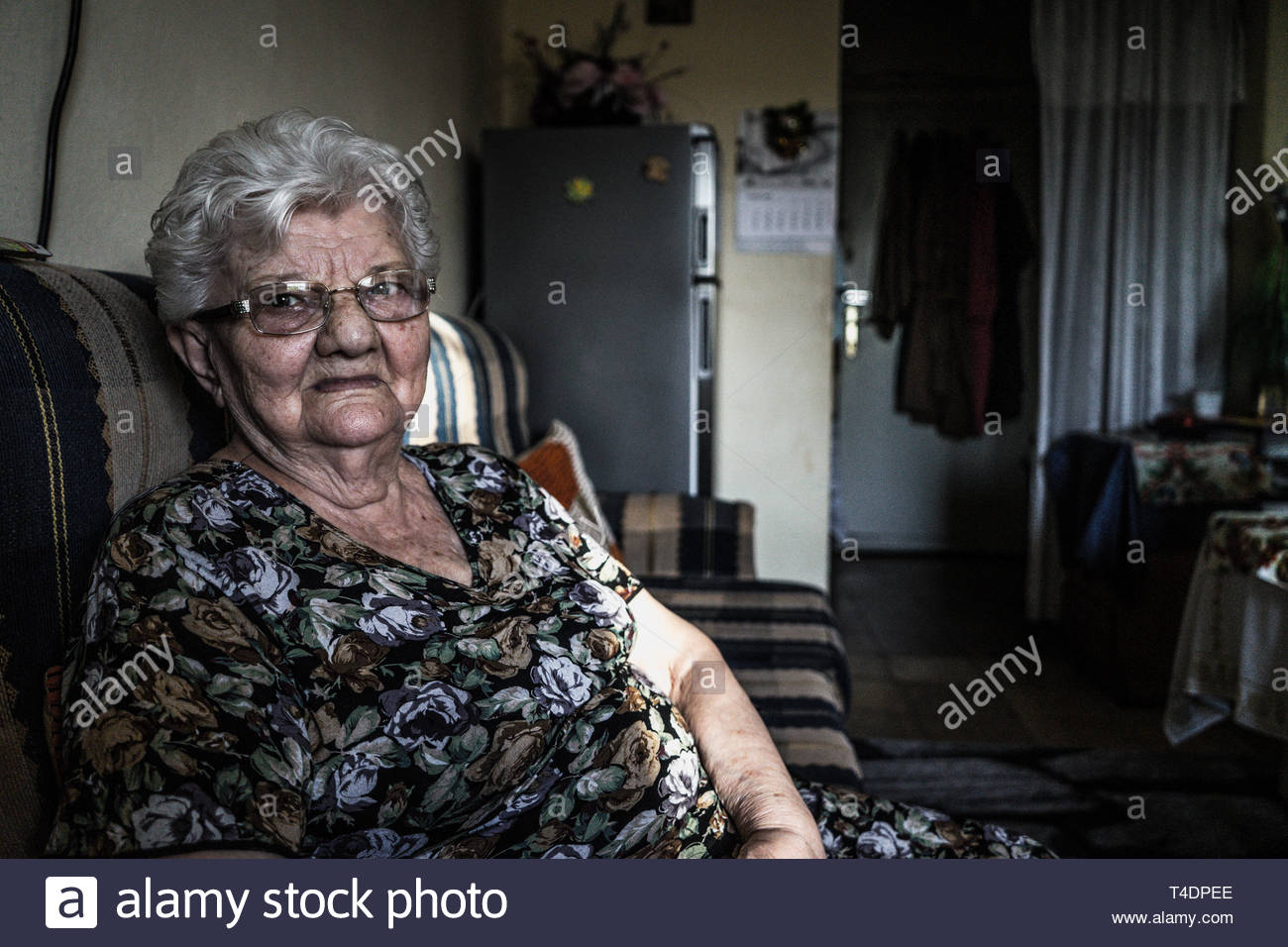 woman wearing blue floral dress sitting on the sofa - Stock Image