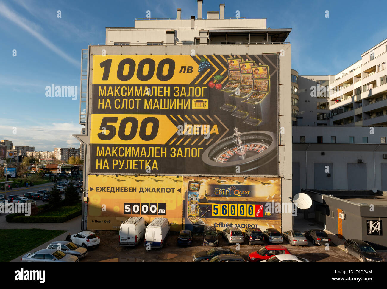 Eastern European absurd urban city surroundings. Cars parked in the dirt by a casino wall advertisement promising big winnings in Sofia Bulgaria. - Stock Image