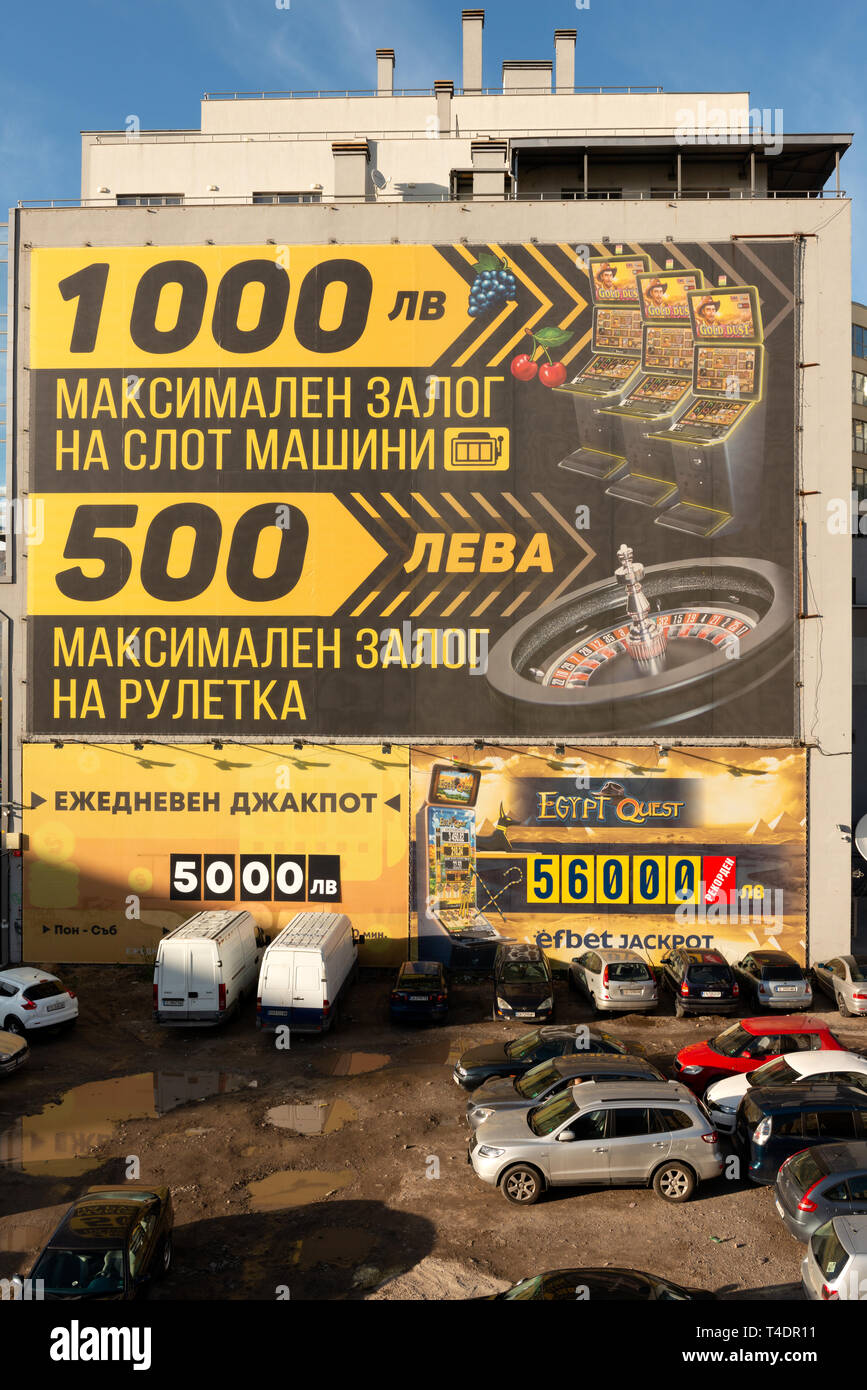 Cars parked in the dirt by a casino wall advertisement promising big winnings in Sofia Bulgaria. Eastern European absurd urban city surroundings - Stock Image