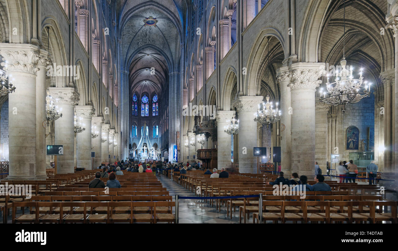 Paris, France - September 11, 2013: People inside the cathedral Notre-Dame de Paris. The cathedral is widely considered to be one of the finest exampl - Stock Image
