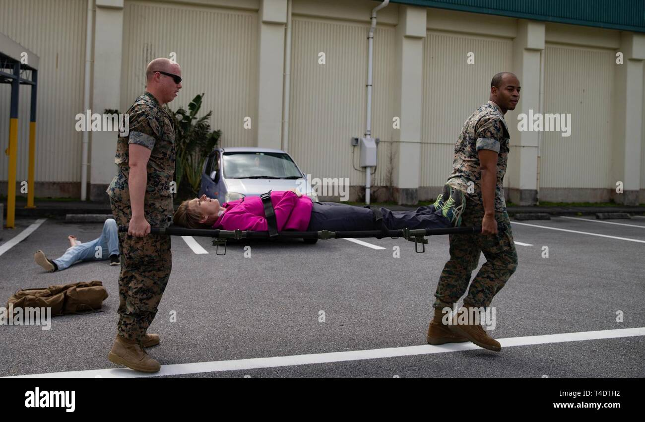 U.S. Navy corpsman help transport a Marine with Headquarters Battalion, 3rd Marine Division, during a Casualty Evacuation Drill on Camp Courtney, Okinawa, Japan, March 26, 2019. Casualty Evacuation Drills allow the U.S. Navy corpsman to practice lifesaving skills in the event of a disaster. - Stock Image