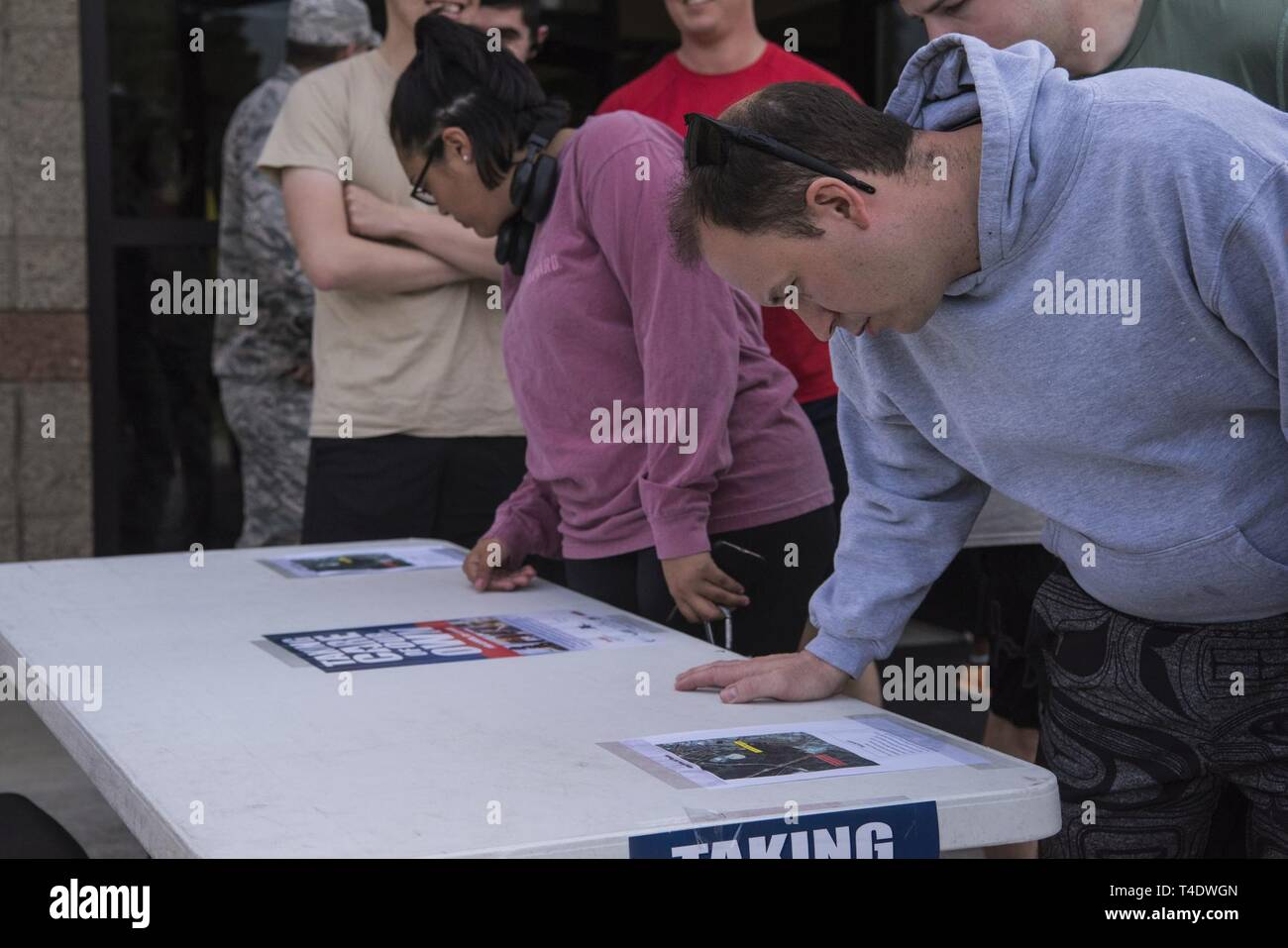 "Airmen and their families look at Air Force Assistance Fund flyers before the AFAF ""Run Because We Care"" 5K March 22, 2019, on Vandenberg Air Force Base, Calif. Vandenberg's AFAF campaign, spanning from March 16 to April 26, 2019, hopes to raise $41,342 for the charity that assists Airmen. - Stock Image"