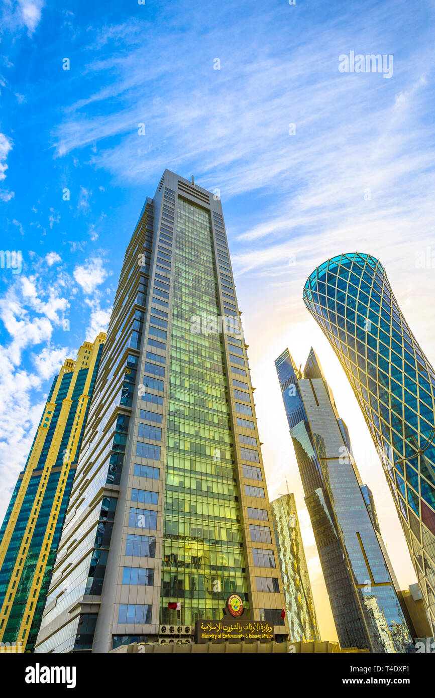 Doha, Qatar - February 17, 2019: bottom view of Ministry Endowment Islamic Affair and Tornado Tower in West Bay commercial district. Skyscrapers in - Stock Image