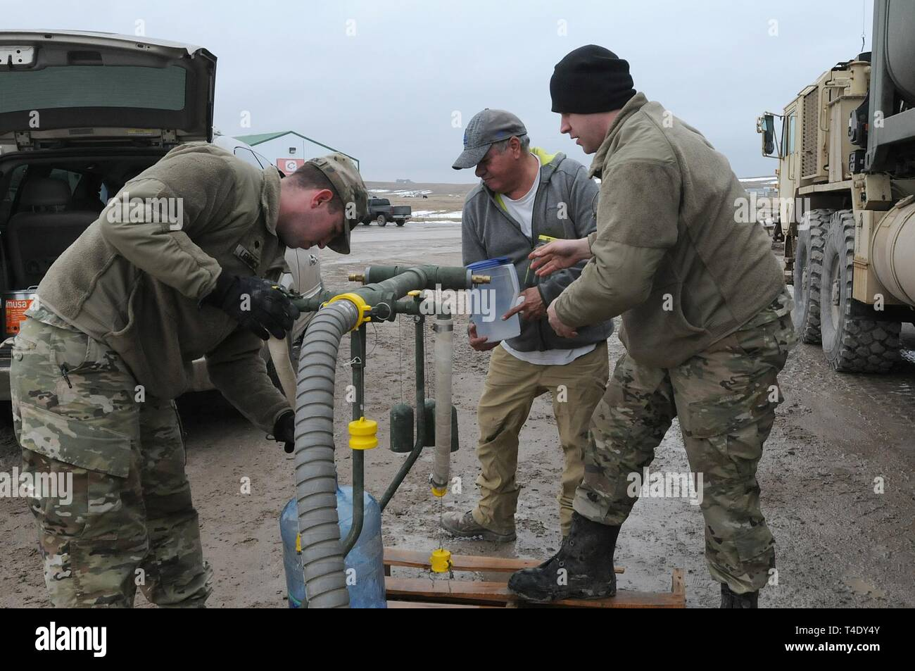U.S. Army Sgt. David Fuegen, right, and Spc. Tracy Lennick, members with Company A, 139th Brigade Support Battalion, South Dakota Army National Guard, provide drinkable water to Lester Iron Cloud at Sharps Corner, S.D, on the Pine Ridge Reservation, March 25, 2019. Thirteen SDARNG Soldiers were activated for state duty in Pine Ridge after a county waterline failed due to extreme flooding leaving residents in seven communities without water in their homes. Stock Photo