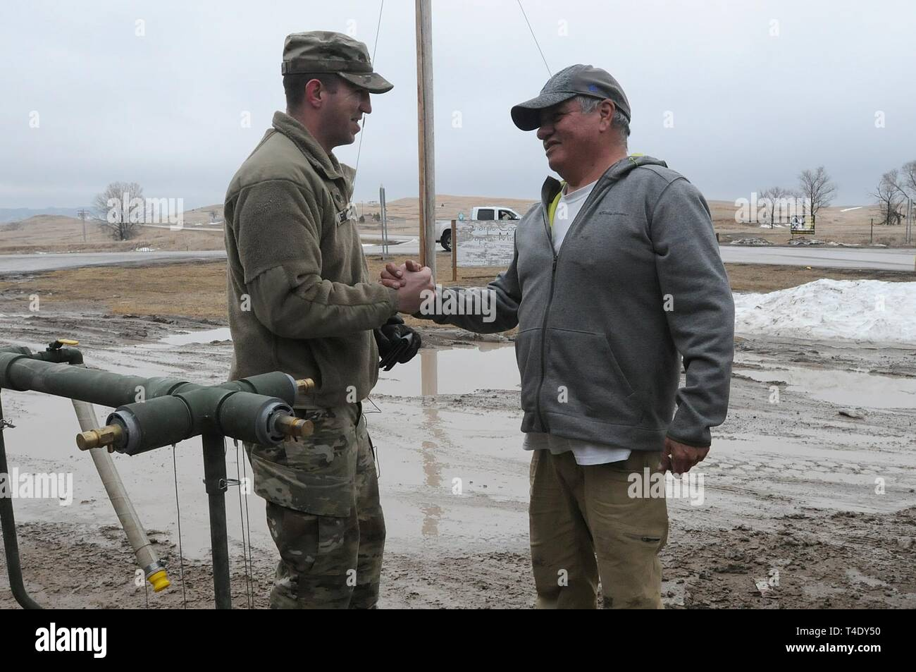 Lester Iron Cloud thanks U.S. Army Spc. Tracy Lennick, with Company A, 139th Brigade Support Battalion, South Dakota Army National Guard, after receiving drinkable water at Sharps Corner, S.D, on the Pine Ridge Reservation, March 25, 2019. Thirteen SDARNG Soldiers were activated for state duty in Pine Ridge after a county waterline failed due to extreme flooding leaving residents in seven communities without water in their homes. Stock Photo