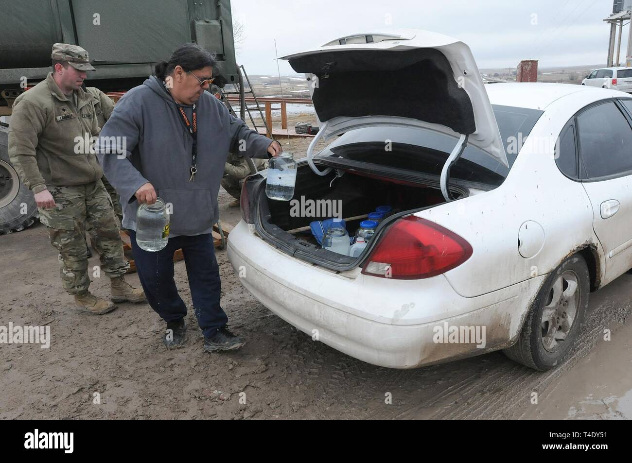 Lester Rowland loads containers of drinkable water into his car with the help of U.S. Army Spc. Tracy Lennick, Company A, 139th Brigade Support Battalion, South Dakota Army National Guard, at Sharps Corner on the Pine Ridge Reservation, March 25, 2019. Thirteen SDARNG Soldiers were activated for state duty in Pine Ridge after a county waterline failed due to extreme flooding leaving residents in seven communities without water in their homes. Stock Photo