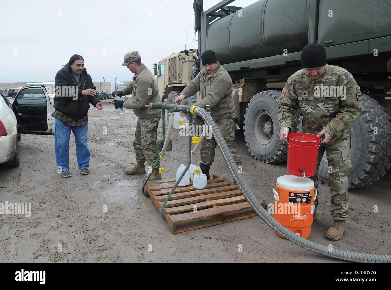 From left) South Dakota Army National Guard Soldiers Spc. Tracy Lennick, Sgt. David Fuegen and Lt. Col. Lew Weber fill containers with drinkable water for residents of Sharps Corner on the Pine Ridge Reservation, S.D., March 25, 2019. Thirteen SDARNG Soldiers with Company A, 139th Brigade Support Battalion, were activated for state duty in Pine Ridge after a county waterline failed due to extreme flooding leaving residents in seven communities without water in their homes. Stock Photo