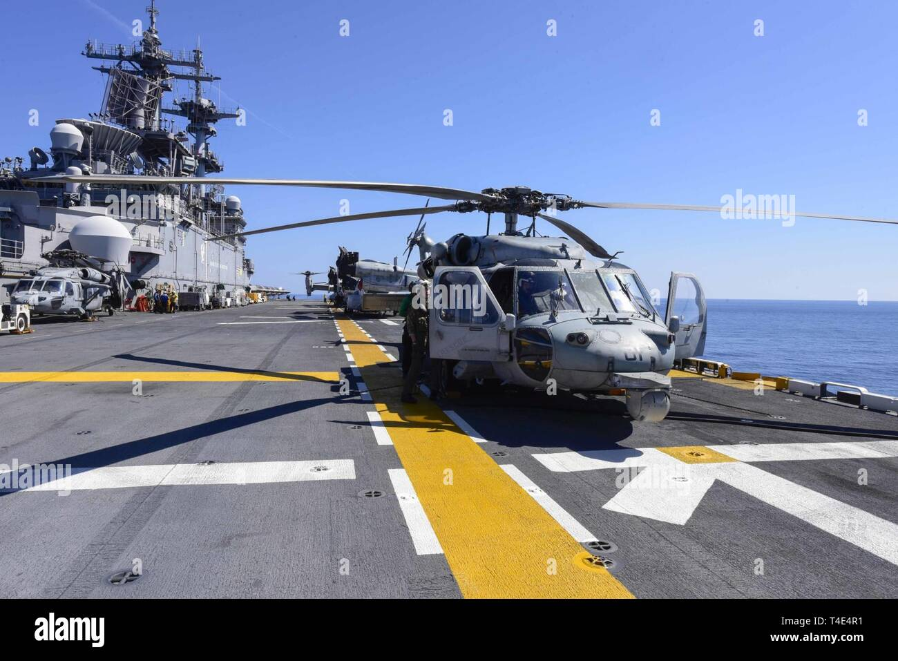 SOUTH CHINA SEA (March 29, 2019) - An MH-60S Sea Hawk, assigned to Helicopter Sea Combat Squadron (HSC) 25, is secured to the flight deck of the amphibious assault ship USS Wasp (LHD 1). Wasp, flagship of Wasp Amphibious Ready Group, is operating in the Indo-Pacific region to enhance interoperability with partners and serve as a lethal ready-response force for any type of contingency. - Stock Image