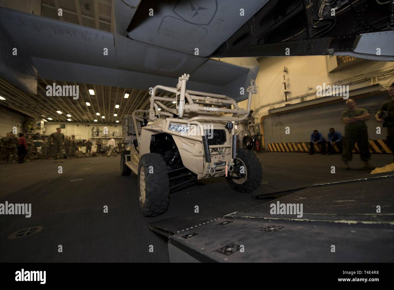 SOUTH CHINA SEA (March 29, 2019) - Marines load an MRZR ultra-light ground mobility vehicle onto an MV-22 Osprey, assigned to Marine Medium Tiltrotor Squadron (VMM) 268, in the hangar bay of the amphibious assault ship USS Wasp (LHD 1). Wasp, flagship of Wasp Amphibious Ready Group, is operating in the Indo-Pacific region to enhance interoperability with partners and serve as a lethal ready-response force for any type of contingency. - Stock Image