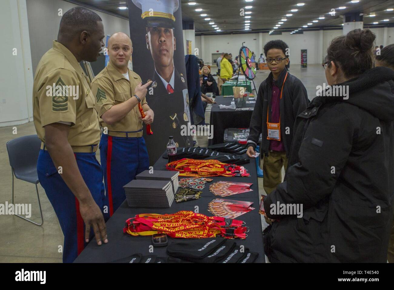 Marine Master Sgt. Damian Cason, a career recruiter with the Marine Corps Recruiting Command, and Sgt. Jacob Droste, a recruiter at Recruiting Substation Wyandotte, talk about the Marine Corps with Nathanael Stewart, a seventh grade student at Betty Shabazz Academy, during a National Society of Black Engineers conference STEAMFest in Detroit, March 30, 2019. NSBE is holding its 45th annual national convention consisting of various programs and workshops that are designed to benefit grade school, collegiate, technical, professional and international attendees and the U.S. Marine Corps is a part Stock Photo