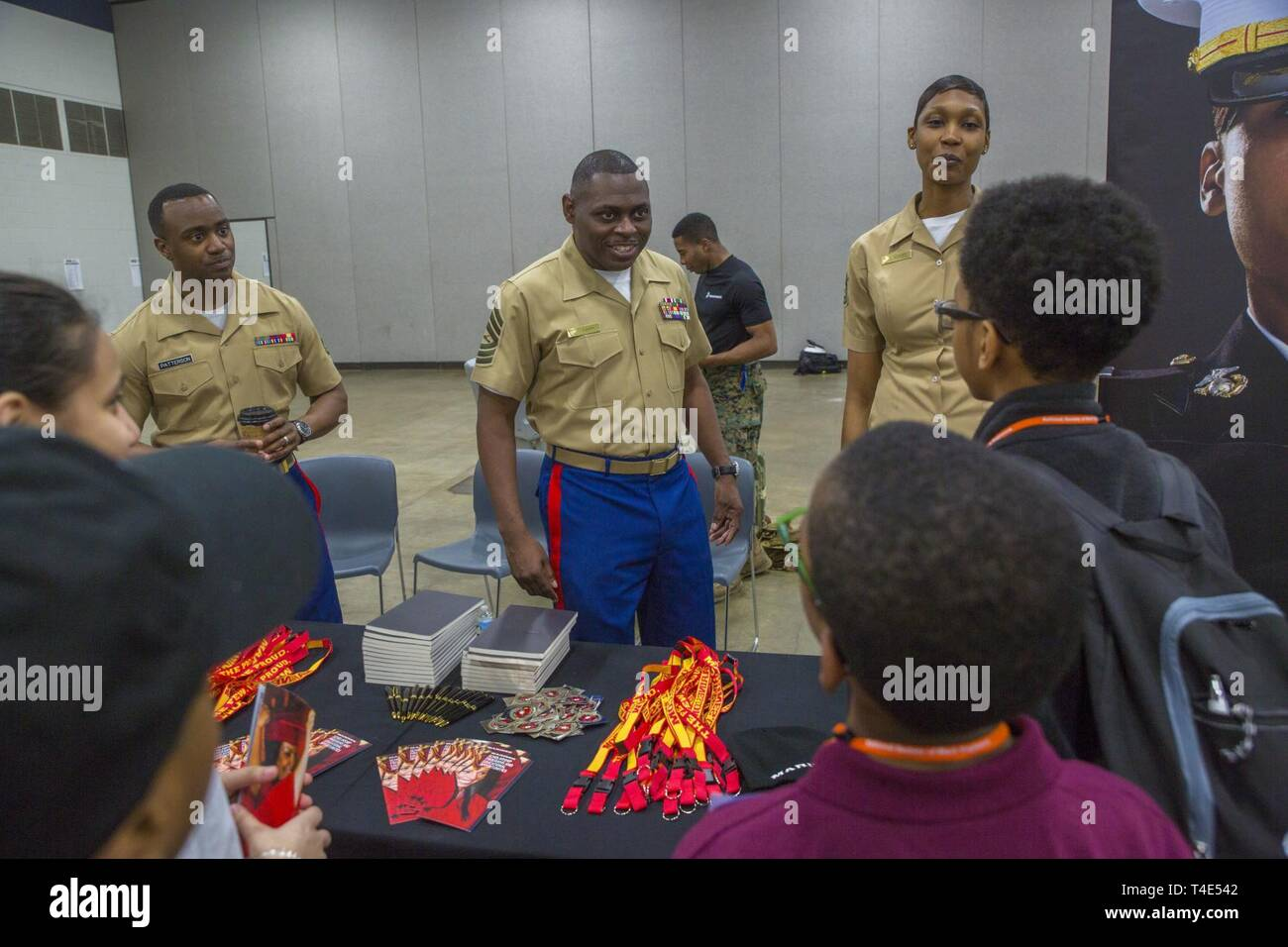 Marine Staff Sgt. Christopher Patterson, a recruiter from Recruiting Station Albuquerque, Master Sgt. Damian Cason, a career recruiter with the Marine Corps Recruiting Command, and Gunnery Sgt. Latyra Sayers, a career recruiter with Recruiting Station San Diego, draw connections between engineering in the Marine Corps and elsewhere to attendees of NSBE during a National Society of Black Engineers conference STEAMFest in Detroit, March 30, 2019. NSBE is holding its 45th annual national convention consisting of various programs and workshops that are designed to benefit grade school, collegiate, Stock Photo