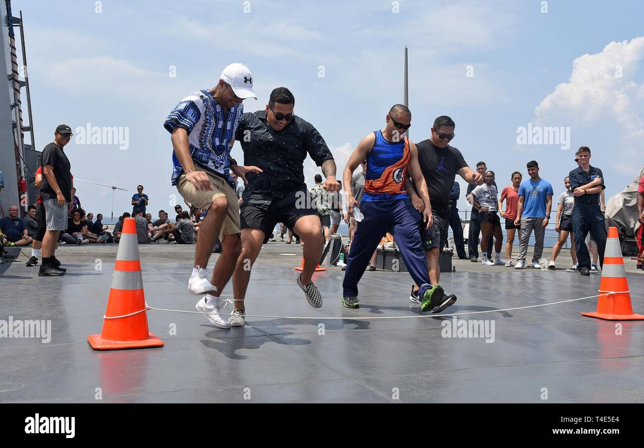SOUTH CHINA SEA (March 31, 2019) - Sailors attached to U.S. 7th Fleet Flagship USS Blue Ridge (LCC 19) participate in a three-legged race during a steel beach picnic. Blue Ridge is the oldest operational ship in the Navy, and as 7th Fleet command ship, is responsible for fostering relationships within the Indo-Pacific Region. - Stock Image