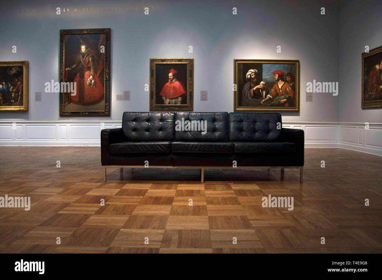 Visitors to the Portland Art Museum in Portland, OR, have the option of resting on leather couches while they examine various paintings. - Stock Image