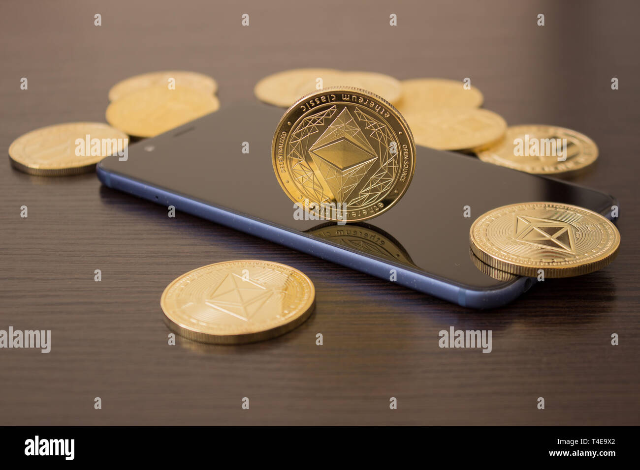 Golden Etherium coin close up on smartphone - business concept of crypto currency. - Stock Image