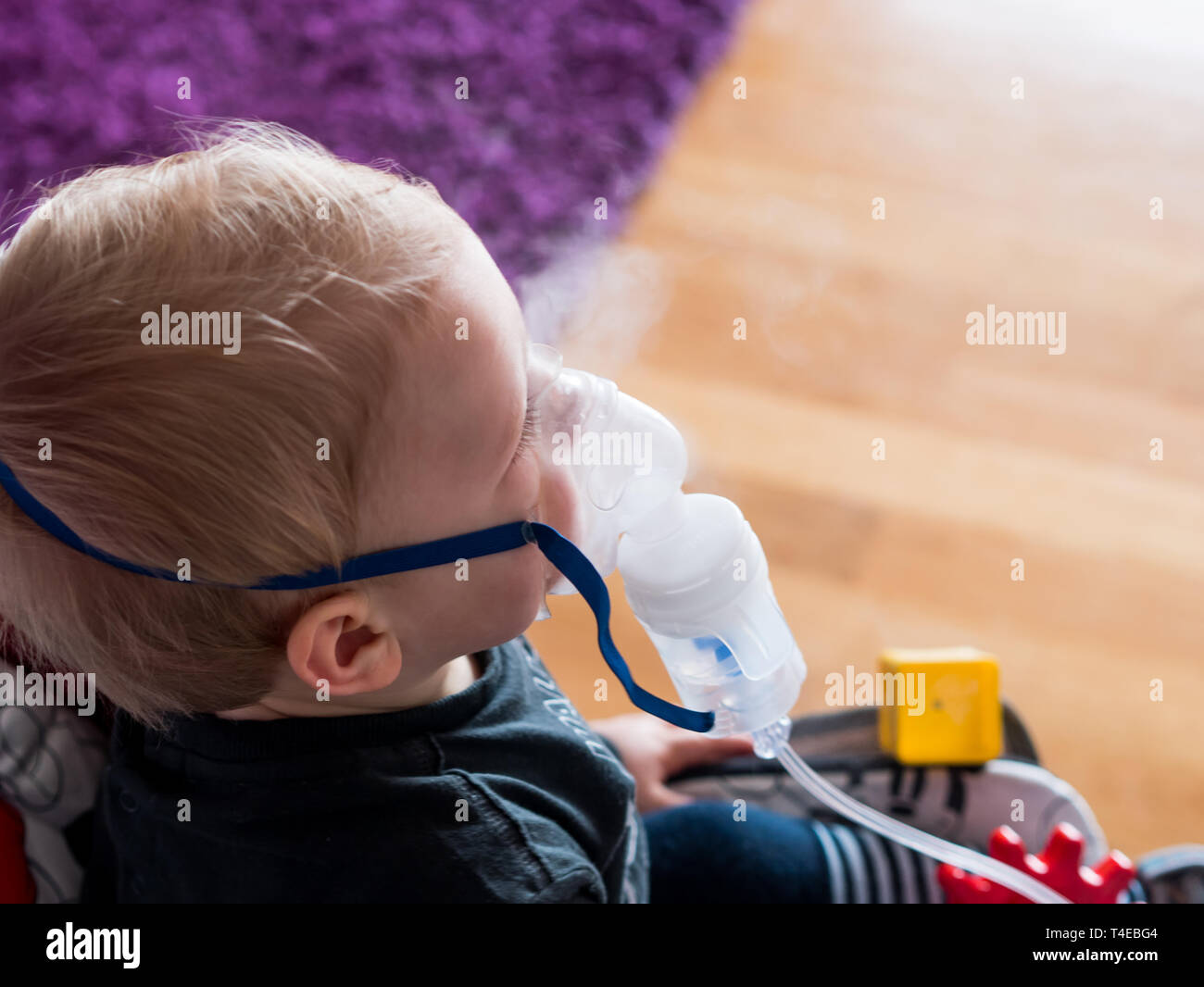 Caucasian boy with oxygen mask at home inhaling - Stock Image