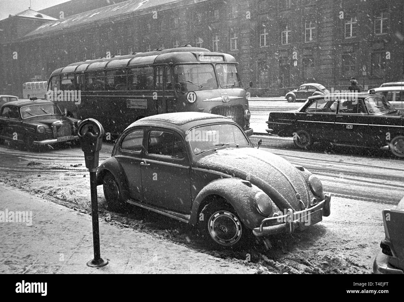 A VW-Käfer is parked in front of a parking meter in the snow (archive picture from the 28th of January in 1963). | usage worldwide - Stock Image