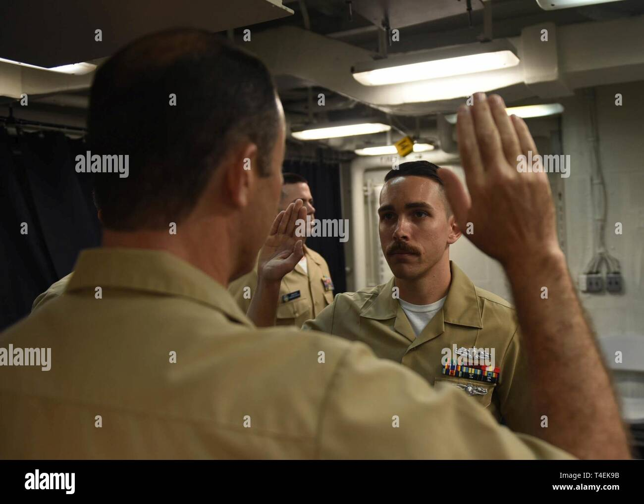SOUTH CHINA SEA (April 1, 2019) - Ensign Dylan J. Rich, from St. Clair Shores, Mich., recites the oath during his commissioning ceremony aboard U.S. 7th Fleet Flagship USS Blue Ridge (LCC 19). Rich, a former hospital corpsman 1st class, was commissioned through the Navy's Health Service Collegiate Program. Blue Ridge is the oldest operational ship in the Navy, and as 7th Fleet command ship, is responsible for fostering relationships within the Indo-Pacific Region. - Stock Image