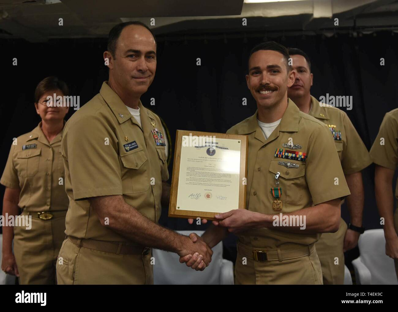 SOUTH CHINA SEA (April 1, 2019) - Ensign Dylan J. Rich, from St. Clair Shores, Mich., poses for a picture with U.S. 7th Fleet Flagship USS Blue Ridge (LCC 19) Commanding Officer Capt. Eric J. Anduze, during his commissioning ceremony. Rich, a former hospital corpsman 1st class, was commissioned through the Navy's Health Service Collegiate Program. Blue Ridge is the oldest operational ship in the Navy, and as 7th Fleet command ship, is responsible for fostering relationships within the Indo-Pacific Region. - Stock Image